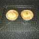 Scotch pies are rested in their casings on a wire rack