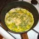 Eggs and herb are added to oil in frying pan