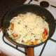 Grated cheese is scattered over the chicken and peppers