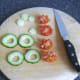 Preparing cherry tomatoes and cucumber garnish