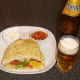 Curried chicken burger in naan bread is served with a glass of Indian beer.