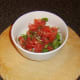 Salsa ingredients are finely chopped and added to a bowl.