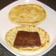 Curried Lorne sausage is laid on naan bread