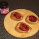Cranberry sauce is spread on wholemeal toast