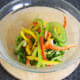 Salad bed ingredients are combined and seasoned in a bowl