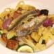 Sardine fillets are laid on tagliatelle and vegetables