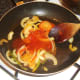 Sweet and sour sauce is added to bell peppers and onion