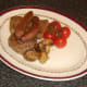 Tomatoes and mushrooms are plated with beef fry up components.