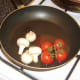 Frying cherry tomatoes and mushrooms.