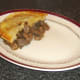 Pastry is laid on top of steak, liver and kidney pie filling.
