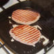 Bacon medallion steaks are turned in griddle pan