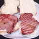 Gammon steaks are laid on bottom halves of bread rolls