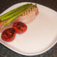 Griddled asparagus and tomato are plated with sweetcure bacon steak