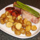 Griddled bacon steak with asparagus and roast potatoes is served