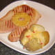 Spicy cheese baked potato is plated with gammon steak and pineapple