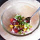 Basil and seasonings are added to the salsa ingredients