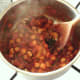 Chickpeas and chopped coriander are added to curry sauce