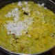 Step six: The bottle gourd and mung beans are almost cooked. Add grated coconut, turmeric powder, jaggery powder, and remaining salt. Mix well.