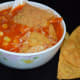 Step six: Garnish with broken nacho chips and grated cheese. Enjoy sipping this delightful Mexican nacho soup!