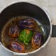 Step five: Heat oil in a cooker base or in a heavy-bottomed pan. Place stuffed brinjal/eggplant one near the other. Cook on low fire for 3 minutes, turning them occasionally to ensure uniform cooking. Add the remaining paste and 1 cup of water.