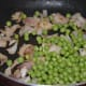 Step two: Add fresh peas. Continue stir-cooking.
