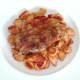 Paprika spiced pork steak is laid on conchiglie pasta