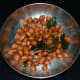 Roast peanuts in a deep-bottomed pan. Transfer them to a plate to keep aside.