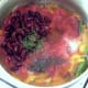 Tomatoes and beans join softened vegetables in the saucepan
