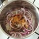 Sliced onion and spices are added to saucepan