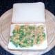 Peas are spread on bottom slice of bread
