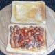 Sardines in tomato sauce are spread on toast