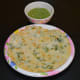 Place two urad dal pancakes on a serving plate. Serve them with a spicy coconut chutney or green chutney on the side. Enjoy!