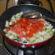 Step four: Add chopped tomatoes. Continue stir-cooking till tomatoes become mushy.
