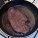 Steak is turned to fry on second side