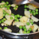Step two: Throw in green peas and potatoes. Add some salt. Stir cook for 2 minutes.