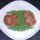 Peas are plated around potato cakes