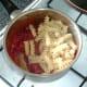 Fusilli pasta is added to tomato sauce