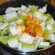 Step two: Put bottle gourd cubes in a deep-bottomed pan or sauce pan. Add some water. Throw in turmeric powder, red chili powder, and salt. Mix well.