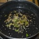 Step five: Add two tablespoons of oil into a non-stick pan. Throw in mustard seeds, curry leaves, and sesame seeds. Saute until mustard pops up.