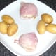 Bacon wrapped mozzarella stuffed garlic mushrooms and buttered new potatoes are plated