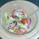 Salad ingredients are stirred through seasoned oil