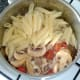 Penne pasta is added to garlic mushrooms and chicken sauce