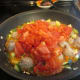 Peeled, and chopped tomatoes being added to the pan.