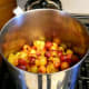 Place the pitted plums in a saucepan, kettle, or stock pot. You can make any amount of jam you like, but a deeper pot requires more stirring and is apt to stick. Two shallow pots are better than one huge one. Add water as necessary. Use low heat.