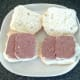 Slices of corned beef are laid on cut open bread rolls