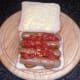 Tomato sauce is spooned on to sausages