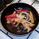 Peppers and onion are flash fried while potatoes drain