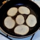 Potato slices are added to hot frying pan seasoned sides down