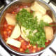 Potatoes and coriander/cilantro are added to chickpea curry