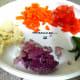 Chopped onions, chopped carrot, chopped cauliflower florets, chopped tomato, and green chillies.